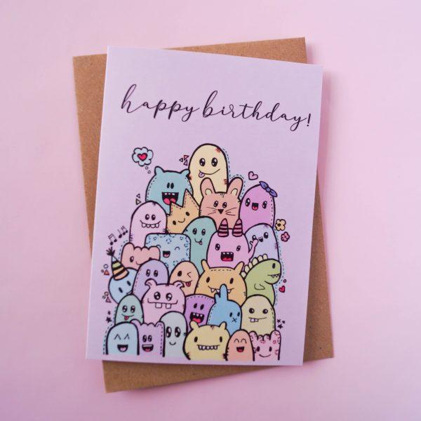 Gevouwen kaart met vrolijke monsters en tekst 'Happy Birthday'